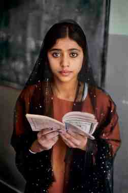 00109_04; Kunduz, Afghanistan, 2002, AFGHN-12156. CAPTION: School Girl in Kunduz.Afghanistan, 2002. NYC65520; MCS2002002 K314 Sikh schoolgirl, Kabul, 2002. 'Most of my images are grounded in people,' McCurry has said, 'and I try to convey what it is like to be that person, a person caught in the broader landscape.' This young girl is studying in one of the few remaining Sikh schools in Kabul. Killed or driven out of the country by the Taliban (who forced Sikhs to identify themselves with yellow badges), many Sikhs are only now beginning to return. As this young girl looks to the future, McCurry captures a rare moment of fragile optimism. - In the Shadow of Mountains Kunduz, Afghanista, 2002 -Portraits In the Shadow of Mountains_Book PORTRAITS_book Retouched_Sonny Fabbri 12/08/2015