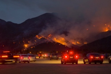 People watch flames as night falls during the Holy Fire near Corona, California. Brushy, drylands in California between Orange and Riverside counties continue to burn, leading to more than 20,000 evacuations from a fire blamed on arson. The Holy Fire has scorched more than 21,473 acres after it ignited in the Cleveland National Forest's Holy Jim Canyon. Thick smoke and ash spewing from the fire prompted air quality warnings. As in many of the wildfires burning across the state, steep terrain in the Holy Fire is making it difficult for fire crews and engines to get close to the flames.