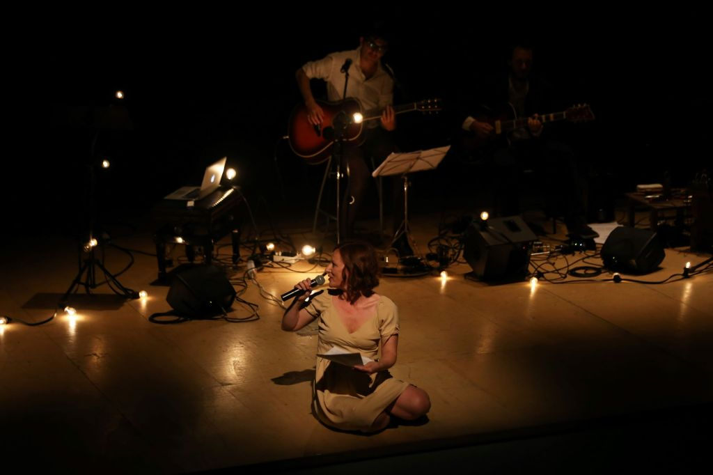 boy-plays-guitar-and-girl-speaking-at-microphone-with-candles-around