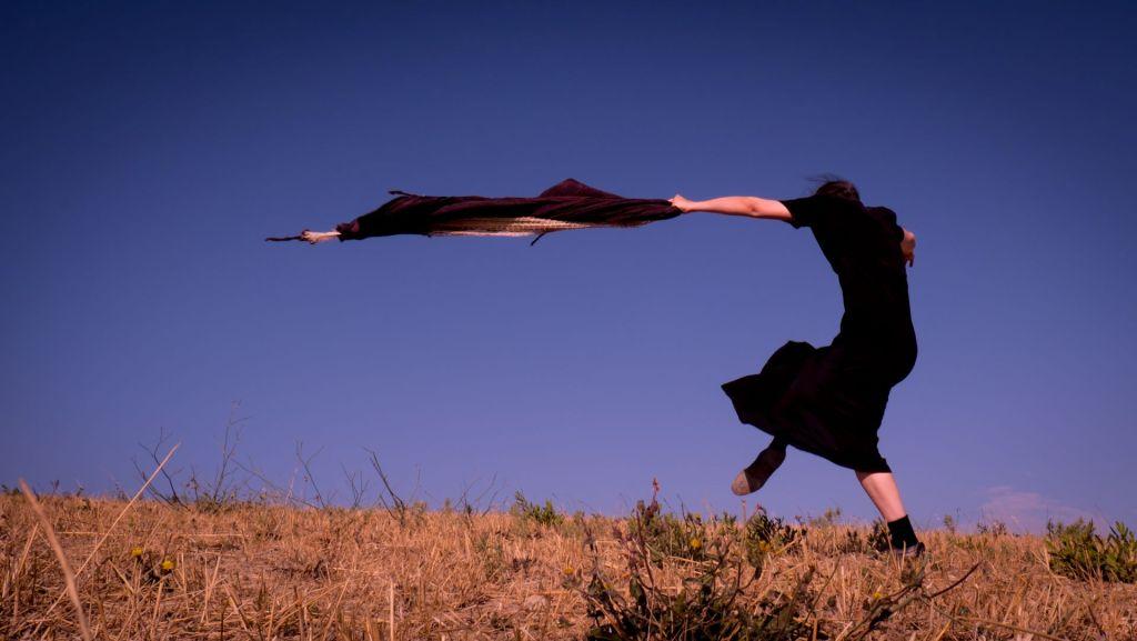 girl-dances-black-dress-sky