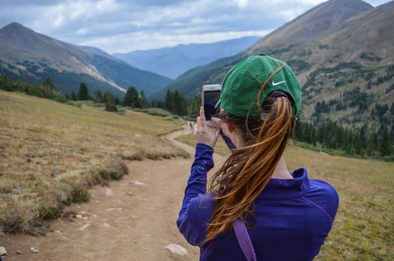 girl-taking-photo-mountain-montagna-cielo-sentiero-berretto-coda-mobile