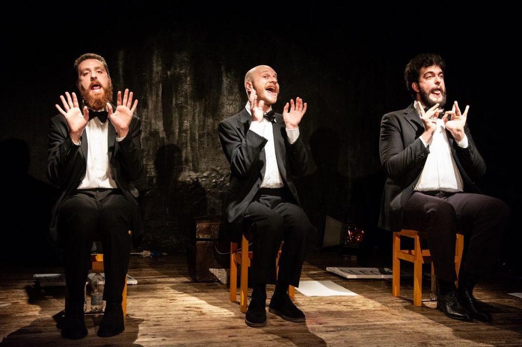 tre-ragazzi-cantano-abito-scuro-barba-palco-men-acting-singing
