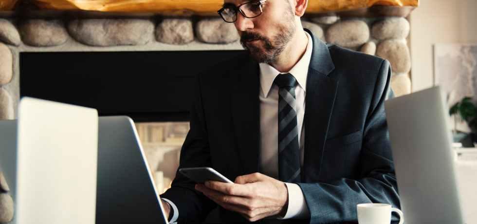 ragazzo-giacca-cravatta-occhiali-barba-computer-caffè-mobile