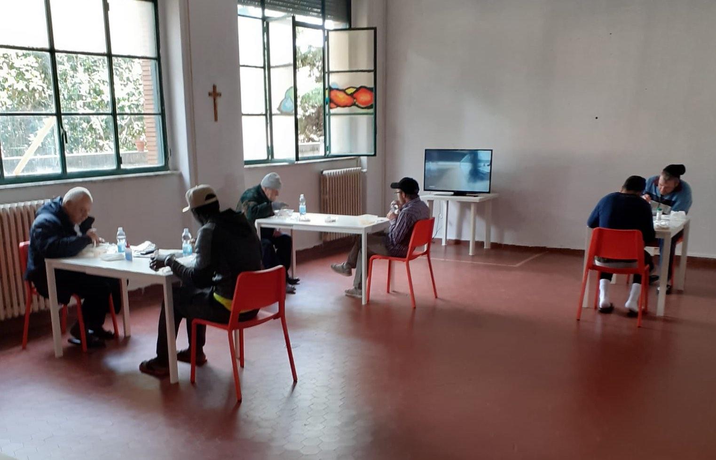 persone-tavoli-sedie-finestre-crocifisso