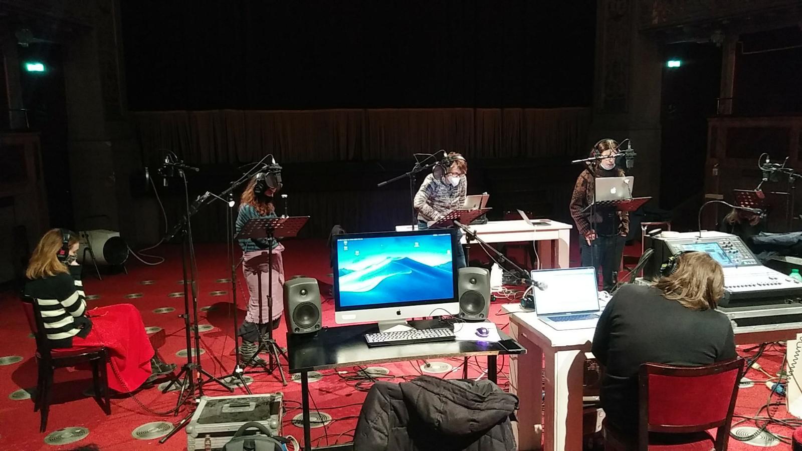 microfoni-schermo-rosso-sedie-persone