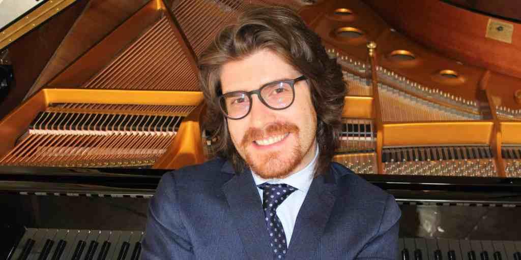 ragazzo-occhiali-pianoforte-giacca-cravatta