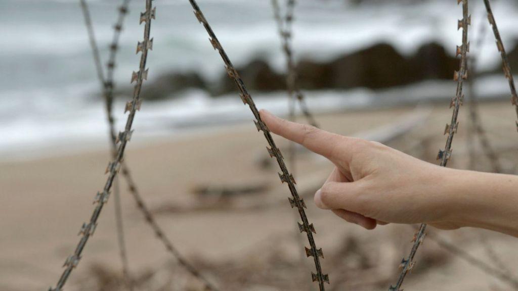 mano-filo-spinato-mare-spiaggia