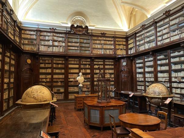 biblioteca-lancisiana-libri-mappamondo-scaffali-tavolo-books-clessidra-busto