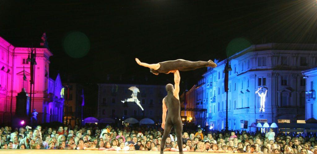 uomo-donna-acrobati-pubblico-ombrello-palazzi