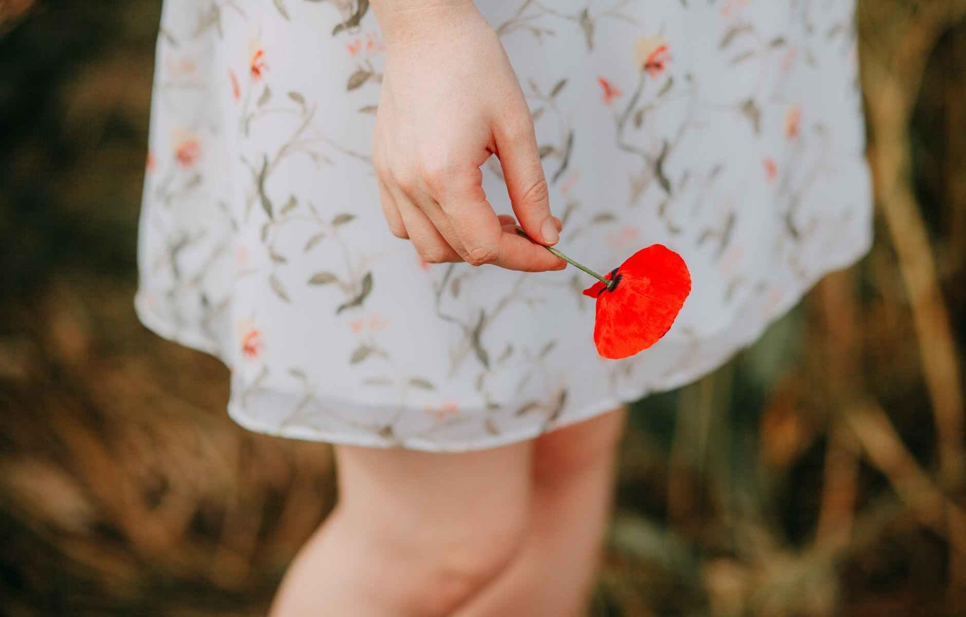mano-fiore-papavero-gambe-donna