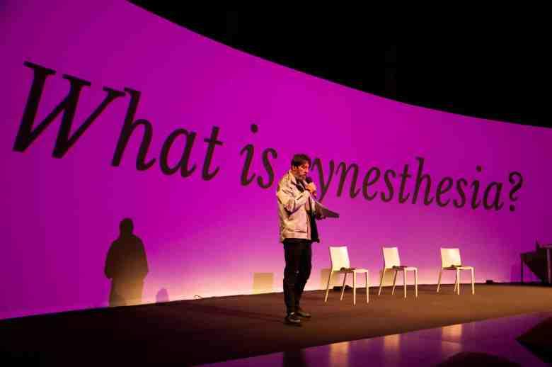 uomo-palco-sedie-schermo-synesthesia