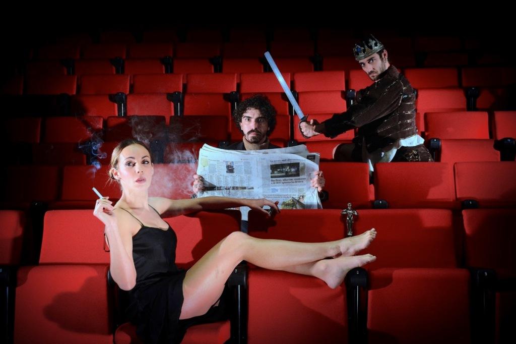 donna-fuma-ragazzo-giornale-spada-poltrone-teatro