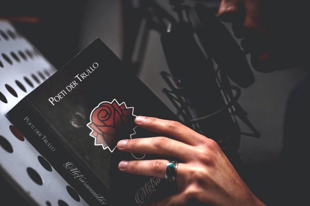 mano-libro-anello-microfono-poeti-der-trullo-leggio